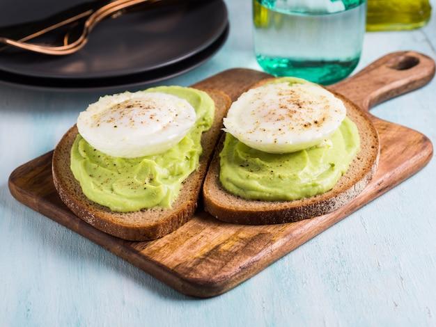 Roggebrood avocado-toast met gepocheerd ei op houten bord. brunch lunch maaltijd