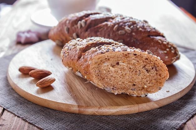 Roggebrood met zonnebloempitten, sesam en vlas op een houten bord.