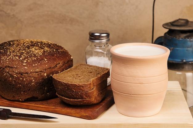 Roggebrood met zout op een snijplank aarden pot met melk en een petroleumlamp