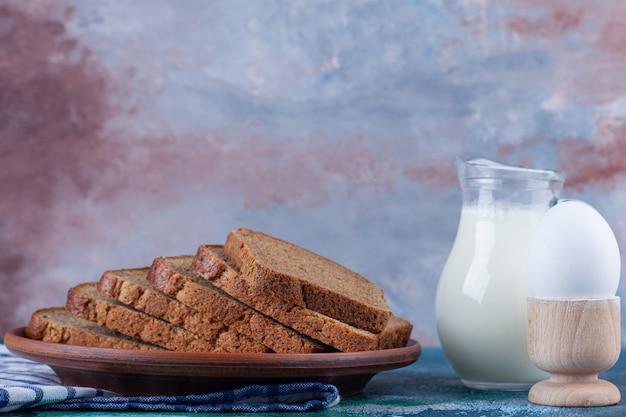 Roggebrood op plaat naast een kruik melk, bloem en ei op handdoek op blauw.