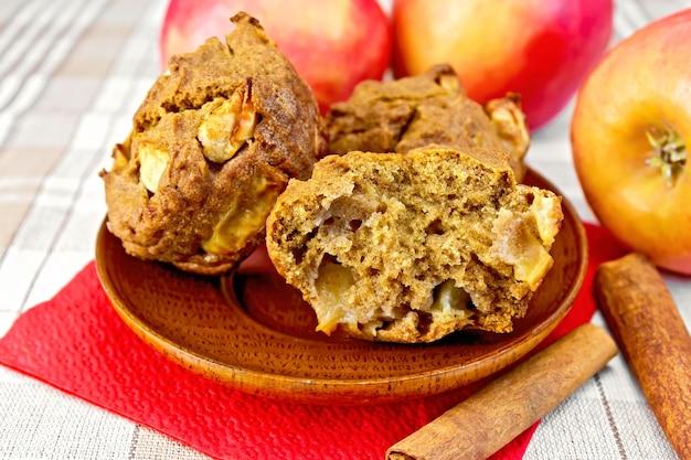 Roggemuffins met appels in een houten bord op een rood papieren servet, appels en kaneel op een achtergrond van een linnen tafelkleed