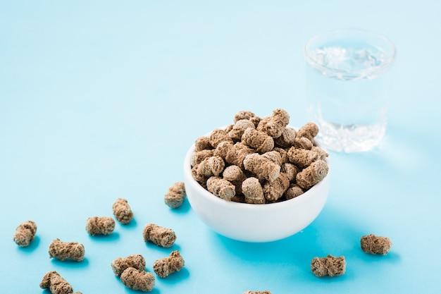 Roggezemelen in een kom en op tafel en een glas water op een blauwe tafel. dieet en het lichaam reinigen met vezels