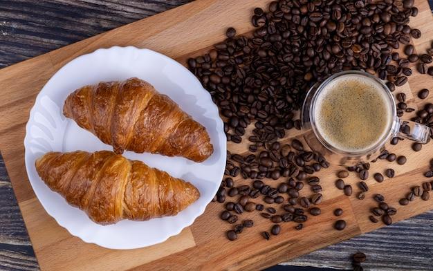 Roissants met een kopje koffie op een houten bord.