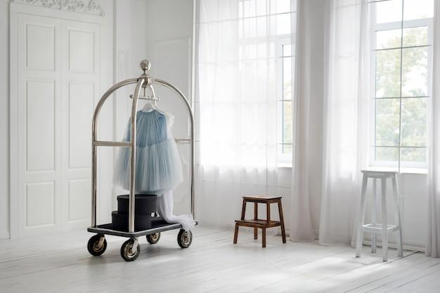 Rok opknoping op mobiele hanger rek in minimalistische witte kamer interieur.