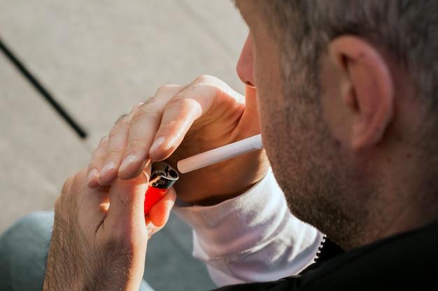 Roken, drugsgebruik, verslaving en slechte gewoontes concept - close-up van jonge man verlichting sigaret buitenshuis. knappe man verlicht sigaret op stedelijke stadsstraat. city mode.
