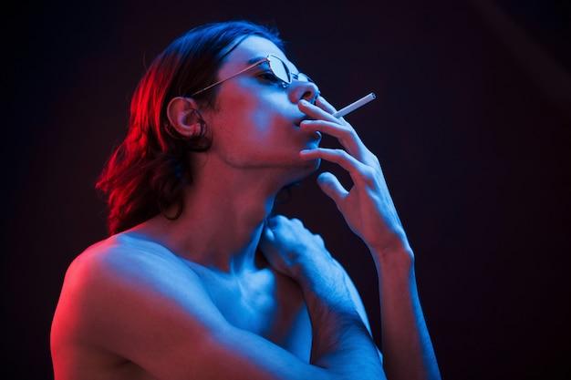 Roken helpt deze man de geest te zuiveren. studio opname in donkere studio met neonlicht. portret van ernstige man