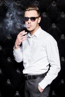 Roken knap. knappe jonge man in wit overhemd roken sigaret en kijken naar camera terwijl staande tegen zwarte achtergrond
