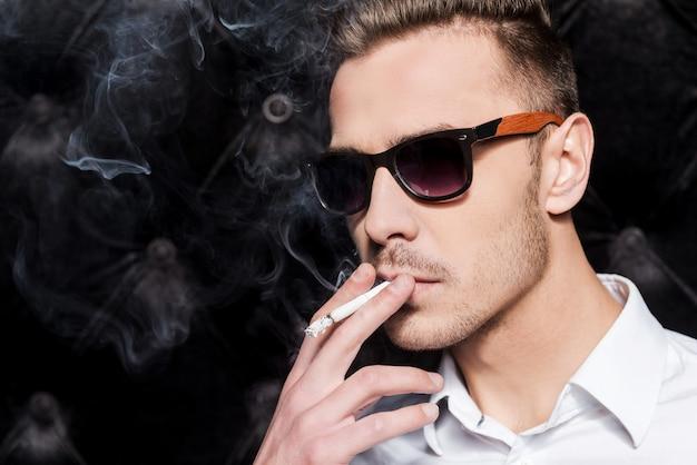 Roken knap. knappe jonge man in wit overhemd roken sigaret terwijl staande tegen zwarte achtergrond
