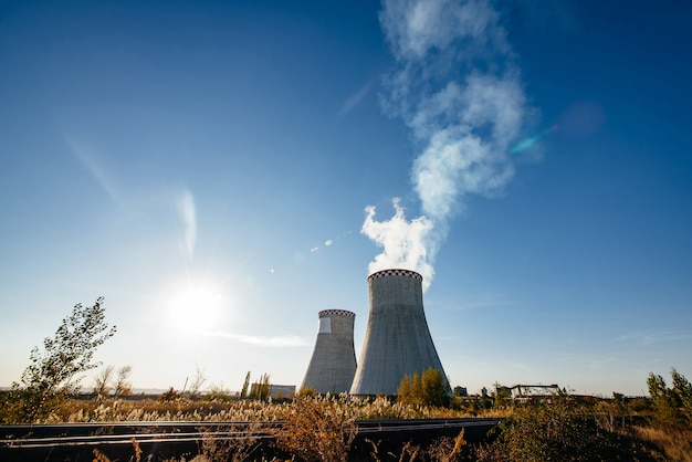 Rokende pijpen van thermische elektrische centrale tegen blauwe hemel