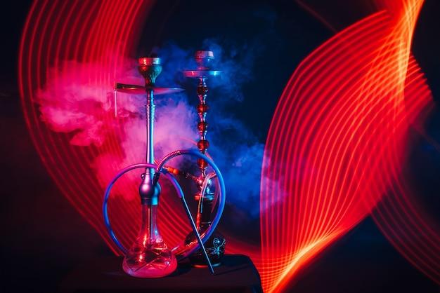 Rokerige turkse waterpijpen met kolen op kommen en water in kolven met rode en blauwe neonlichten op een donkere achtergrond