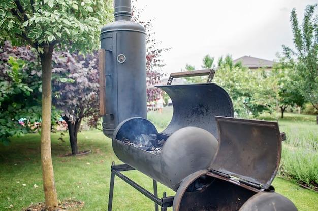Rokersgrill in de achtertuin van het huis, familieterras, buiten bbq-feest op de achtergrond van de groene tuin in de open lucht