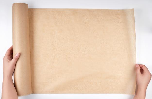 Rol bruin perkamentpapier voor het bakken van voedsel in vrouwelijke handen