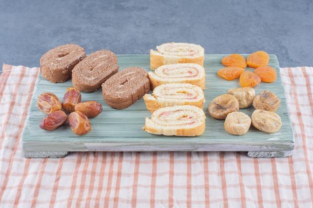Rol cake en gedroogd fruit op het bord, op de marmeren achtergrond.