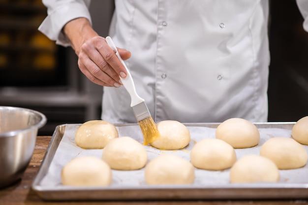 Rol, dekkend glazuur. mans hand met borstel aanraken oppervlak van broodjes liggend op bakplaat, zonder gezicht