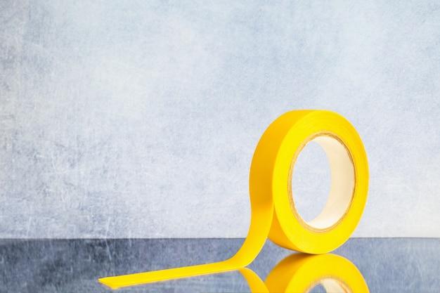 Rol gele elektrotape op een grijze achtergrond