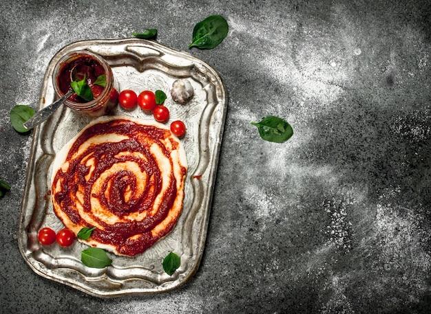 Rol het deeg op met tomatensaus en diverse ingrediënten. op een rustieke achtergrond.