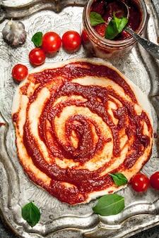Rol het deeg op met tomatensaus en diverse ingrediënten.