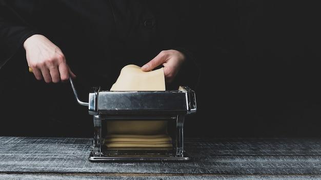 Rol het deeg uit op een pastamachine op een donkere houten tafel