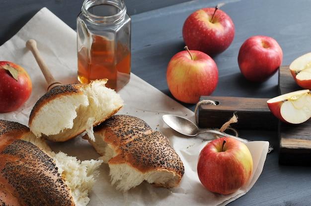 Rol met maanzaad, in stukken gescheurd close-up shot met appels en honing