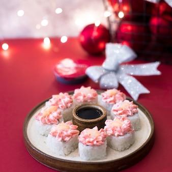 Rol met roomkaas op rood met slingerlichten. sushibroodjes gegarneerd met roze room en garnalen