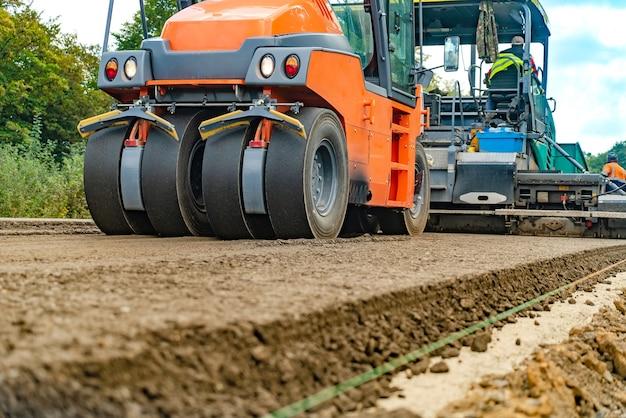 Rol op het nieuwe hete asfalt. wals die aan de nieuwe wegenbouwplaats werkt