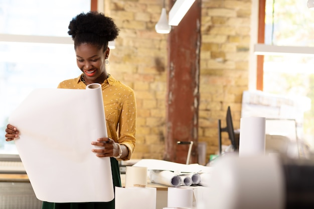 Rol papier. donkere, mooie stijlvolle werknemer van uitgeverij die een rol papier vasthoudt