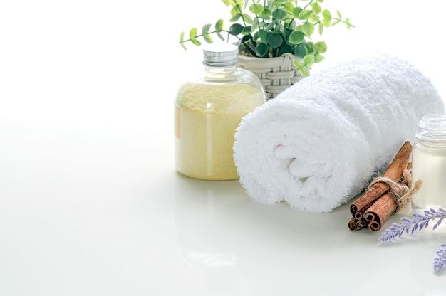 Rol schone handdoek met scrubpoeder en oliefles op witte tafel op, kopieer ruimte voor productvertoning.