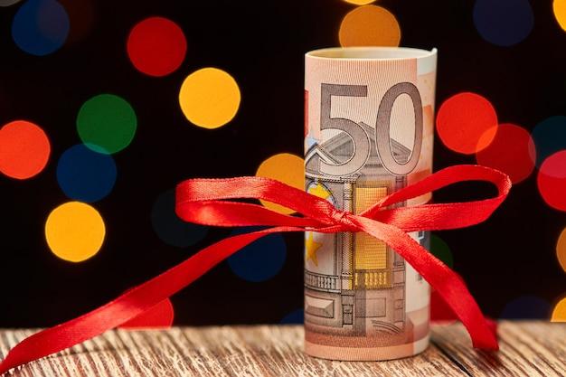 Rol van 50 euro rekeningen met lint tegen kleurrijke lichten