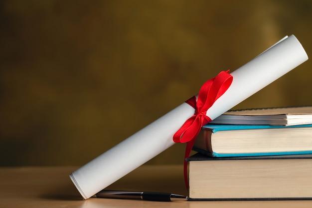 Rol van certificaat, boeken, pen op houten tafel met copyspace