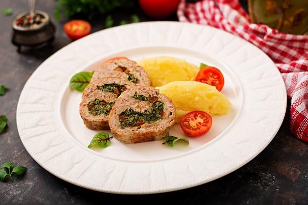Rol van kalkoengehakt met spinazie en rode paprika met garnituur van aardappelpuree