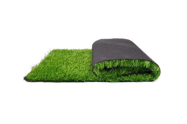 Rol van kunstmatig plastic groen gras dat op witte muur wordt geïsoleerd.