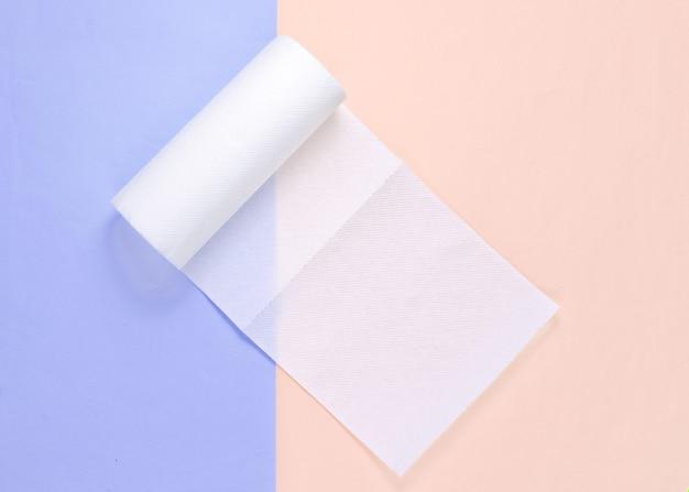 Rol van papieren handdoeken op blauw roze pastel achtergrond