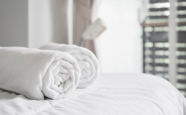 Rol van witte schone badhanddoeken op het bed in de hotelkamer. kopieer ruimte.
