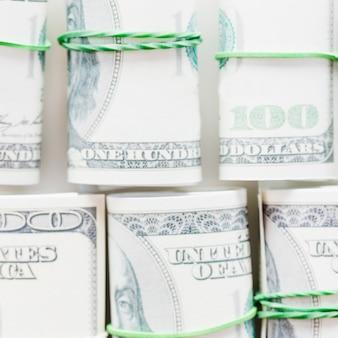 Rolde honderd dollarrekeningen op die met groen rubber worden gebonden