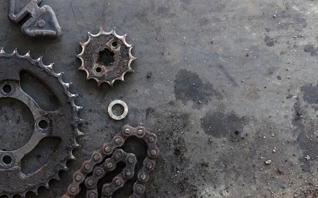 Rolkettingen met tandwielen voor motorfietsen op oude zwarte achtergrond. bovenaanzicht