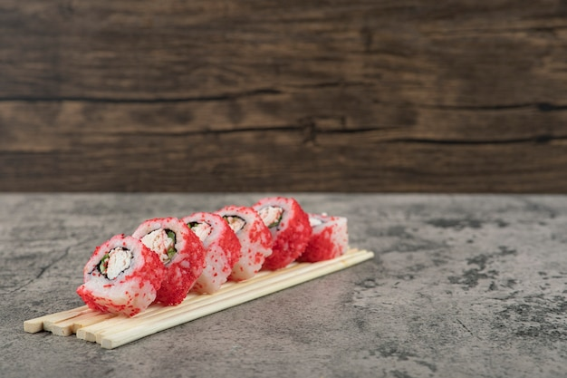 Roll sushi met stokjes op een stenen achtergrond.