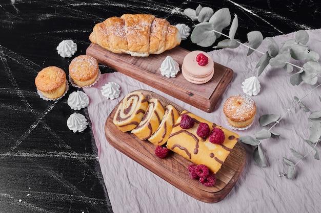 Rollcake met bessen op een schotel met muffins.