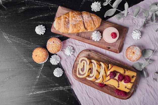 Rollcake met frambozen op een schotel met muffins.