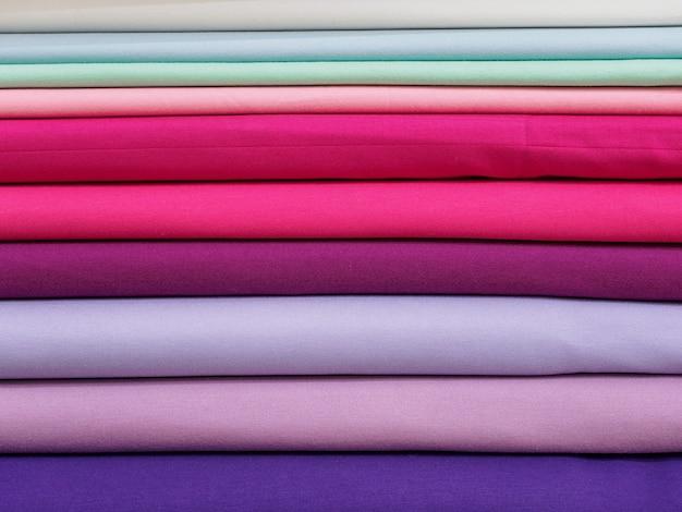 Rollen felgekleurde stof worden netjes op een rij gestapeld in de winkelrekken, close-up.