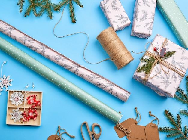 Rollen met inpakpapier, bruin touw, schaar, decor en een ingepakte vierkante doos met een geschenk