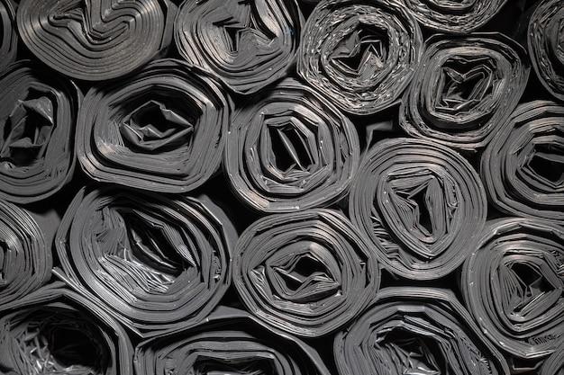 Rollen plastic zakken. gestructureerde achtergrond. veel zwarte opgerolde tassen voor bouwafval.