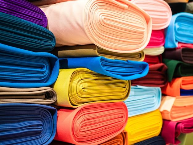 Rollen van fel veelkleurige stof close-up. in de winkel liggen rollen stof op de planken.