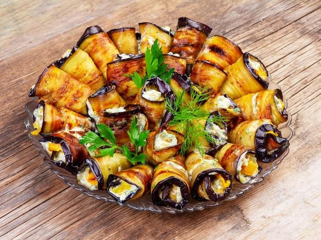 Rollen van gebakken aubergine gevuld met tomaten en knoflook op een houten achtergrond