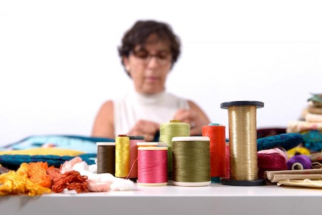 Rollen van gekleurde draden, naaister onderaan