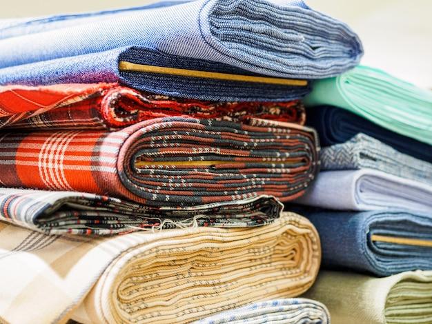 Rollen van verschillende geruite stoffen voor het naaien van jassen close-up.