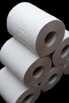 Rollen wc-papier geïsoleerd op zwarte achtergrond in close-up