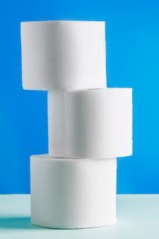 Rollen wc-papier op een blauwe achtergrond. paniekaankoop van essentiële goederen. de coronavirus-epidemie.