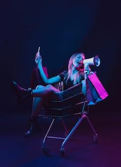Rollend in een karretje met boodschappentassen en megafoon. portret van een jonge vrouw in neonlicht op donkere achtergrondkleur. de menselijke emoties, zwarte vrijdag, cybermaandag, aankopen, verkoop, financieel concept.