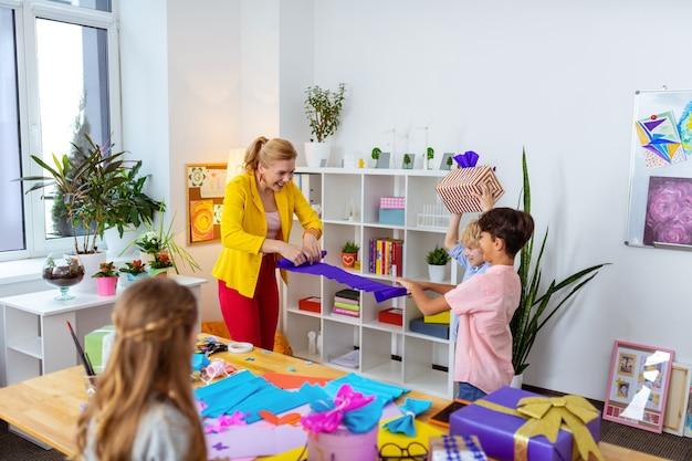 Rollend kleurrijk papier. blonde leraar en schooljongen die kleurrijk papier rolt na een leuke kunstles met haar leerlingen