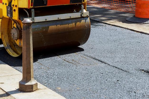 Roller en werknemers bij het asfalteren en repareren van stadsstraten